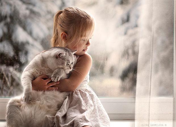 ภาพถ่ายเด็กกอดแมวที่หน้าต่าง