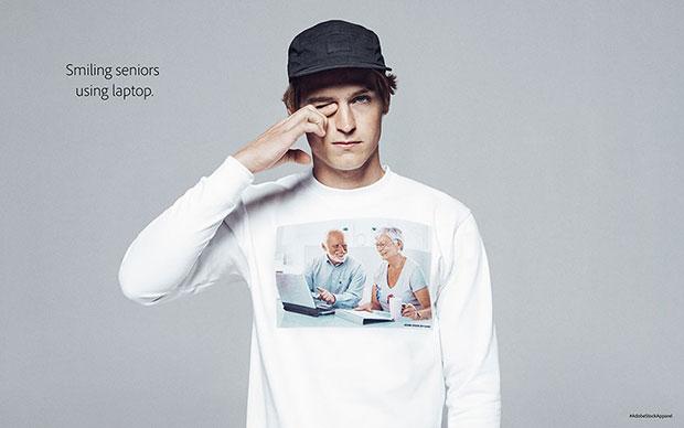 Adobe เสื้อลายสกรีนผู้สูงอายุนั่งเล่นโน๊ตบุ๊คพร้อมกับยิ้มไปด้วย